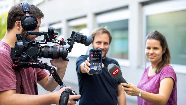 3 persunas cun ina camera, in telefonin ed in microfon