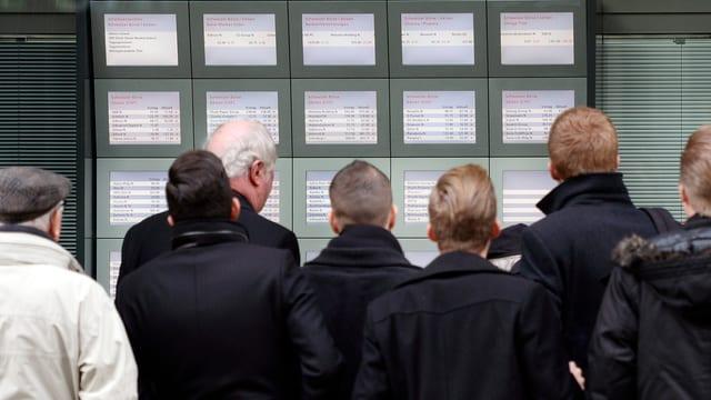 Eine Gruppe von Männern schaut sich Kursanzeigen in einem UBS-Schaufenster in Zürich an.