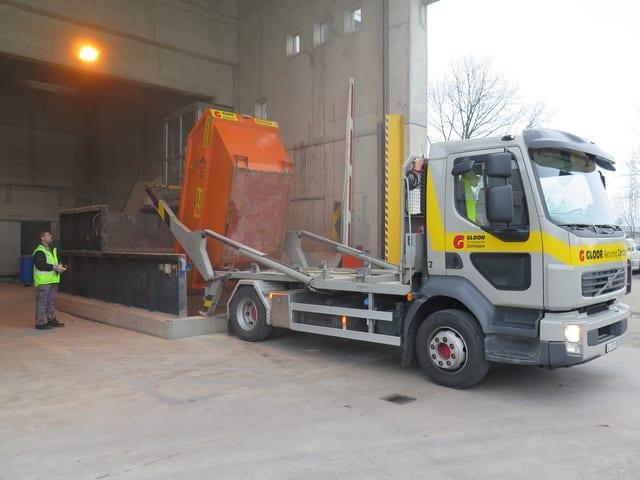 Lastwagen kippt orange Muld aus.