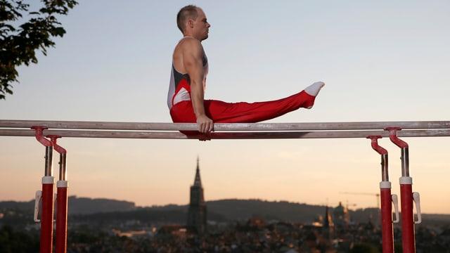 Claudio Capelli turnt zu Werbezwecken eine Barren-Übung mit der Stadt Bern im Hintergrund.