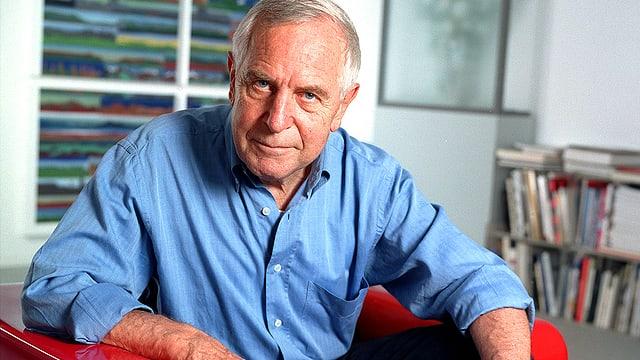 Portrait des Medienethikers Peter Studer. Er sitzt in einem blauen Hemd in einem roten Sessel.
