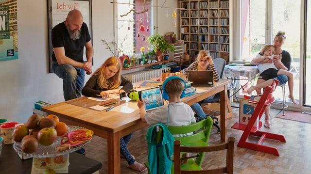 Eltern und Kinder sitzen rund um einen Tisch.