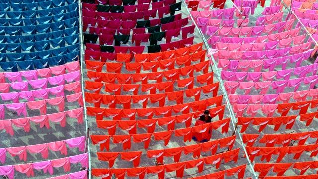 Ein Arbeiter hängt verschieden gefärbte Kleidung zum Trocknen auf eine Leine.