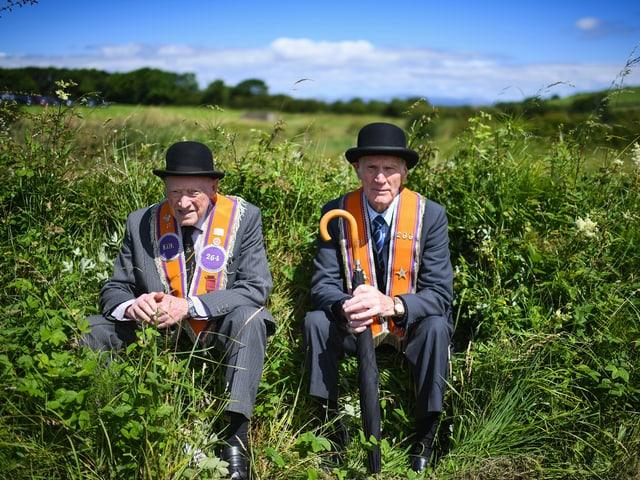 Zwei Männer sitzen im Gras