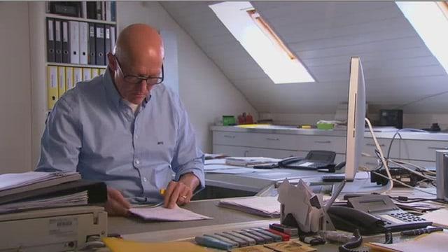 Ein Mann sitzt am Schreibtisch und liest einen Brief