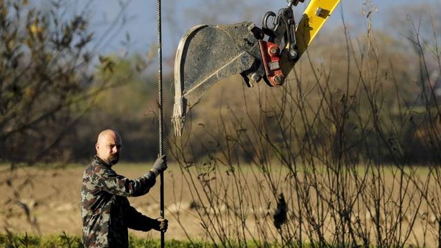 Ein Mann errichtet einen Grenzzaun.