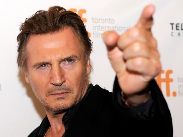 Liam Neeson posiert vor dem Plakat des Toronto International Film Festival.