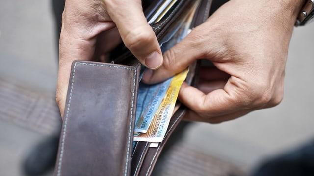Hand hält Banknoten in Portemonnaie.