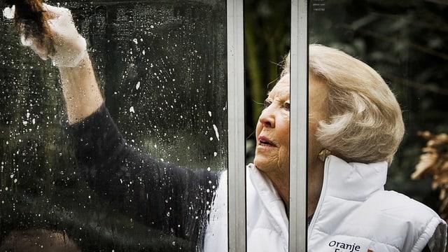 Prinzessin Beatrix putzt ein Fenster.