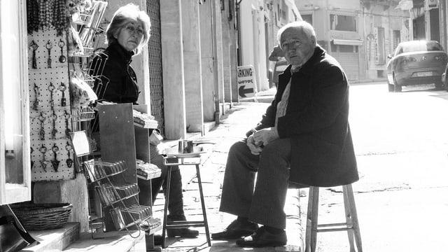 Schwarzweissbild: Eine Frau und ein Mann sitzen auf Stühlen am Strassenrand