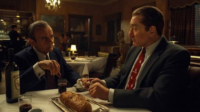 Filmszene aus The Irishman: Zwei Mänenr sitzen im Restaurant an einem Tisch.