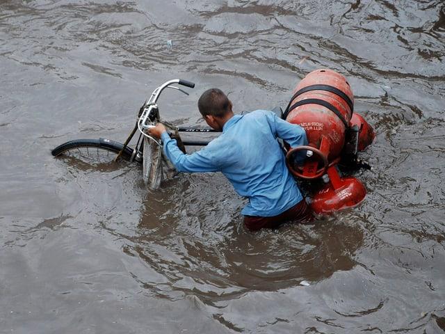 Ein Mann schieb sein Fahrrad durch die Fluten. Auf dem Fahrrade hat der drei Gasflaschen befestigt.