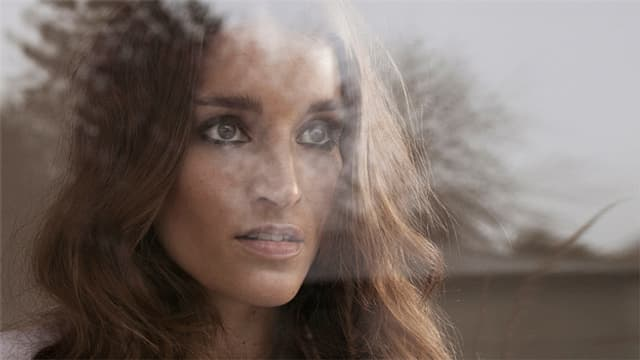 Zu sehen ist Lina Button, fotografiert von der Aussenseite einer Glasscheibe. Etwas Buschwerk spiegelt sich im Glas.