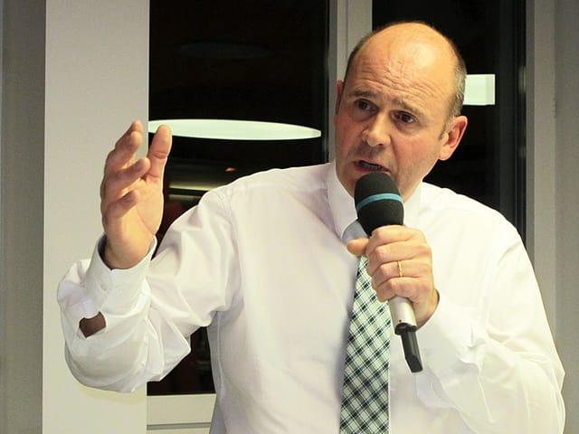 Porträt von Thomas Hurter, der ins Mikrofon spricht.