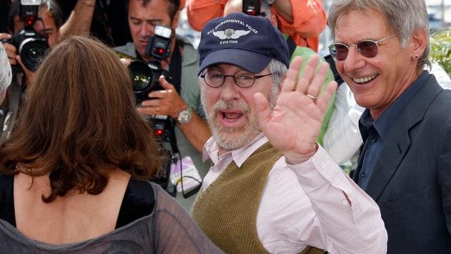 Steven Spielberg winkt in die Kamera, rechts neben ihm steht Indiana Jones-Darsteller Harrison Ford.