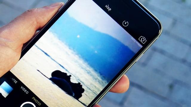 Eine Hand hält ein Smartphone. Darauf ist die Kamera-App zu sehen, das Bild zeigt ein Schlauchboot auf einem Meer.