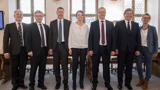 Fünf Männer und zwei Frauen stehen in einer Reihe.