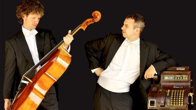 Die beiden Cellisten posieren neben einer Registrierkasse.