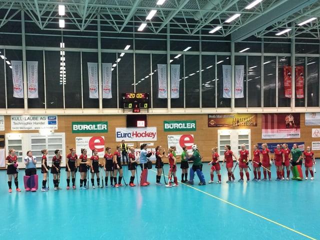 Turnhalle mit blauem Boden, Frauen in Sportbekleidung in Reih und Glied.
