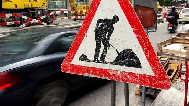 Ein grosses Bauarbeiter-Schild vor dem rollenden Verkehr