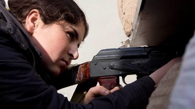 Frau mit Gewehr in der Hand.