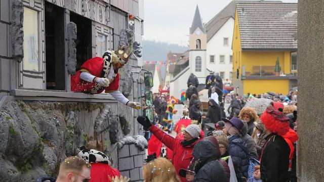 """König gibt ein Glas Bier an die Zuschauer, aus dem Fenster seiner """"Burg"""""""