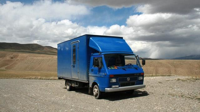 Ein blauer, umgebauter VW-Bus vor hügeliger Landschaft.