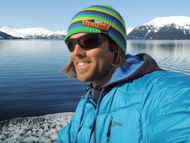 Ueli Kestenholz mit Sonnenbrille vor einem See mit Bergen im Hintergrund posierend.