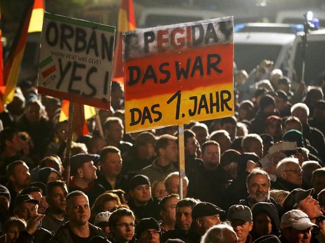 Pegida-Demonstranten am ersten Jahrestag der Kundgebungen. Teilnehmer tragen ein Plakat mit der Aufschrift «Pegida, das war das 1. Jahr» und «Orban, yes».