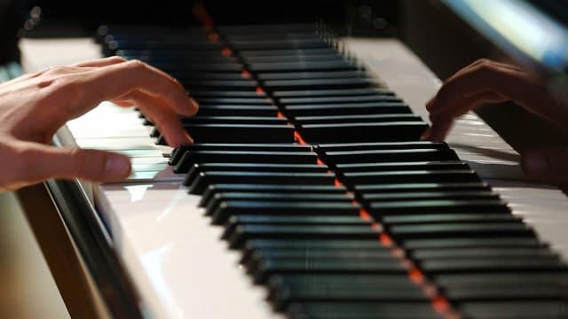 Blick auf die Tasten eines Klaviers, die gespielt werden, allerdings nur von einer linken Hand.