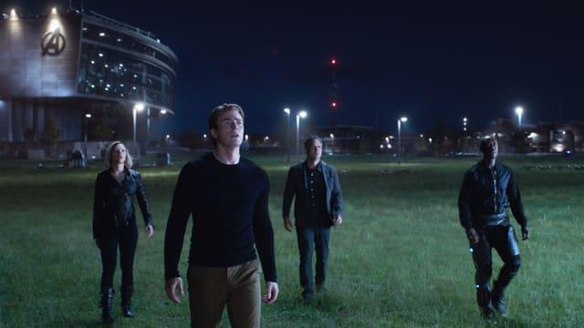 Filmszene: Eine Frau und drei Männer stehen in der Nacht auf einer Wiese und schauen nach oben.