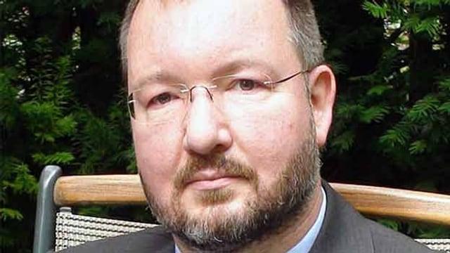 Ein Mann mit Brille und Halbglatze und Bart.
