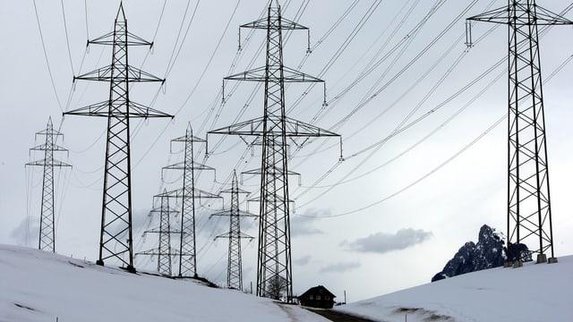 Stromleitungen und -masten in winterlicher Landschaft.
