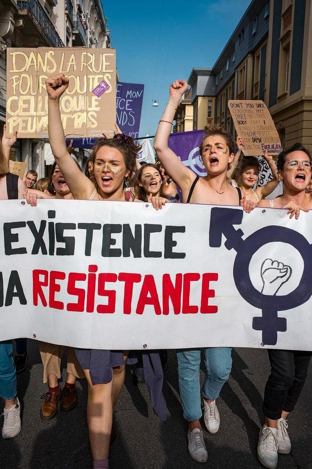 Demonstrantinnen gehen mit Transparenten und erhobenen Armen rufend durch eine Strasse