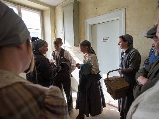 Arbeiter vor Fabrikbüro, z.T. mit Lohnsäckchen in Hand
