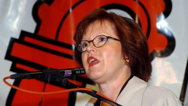 Alt-Regierungsrätin Elsbeth Schneider bei einer Rede am Mikrophon. Im Hintergrund eine Baselbieter Fahne.