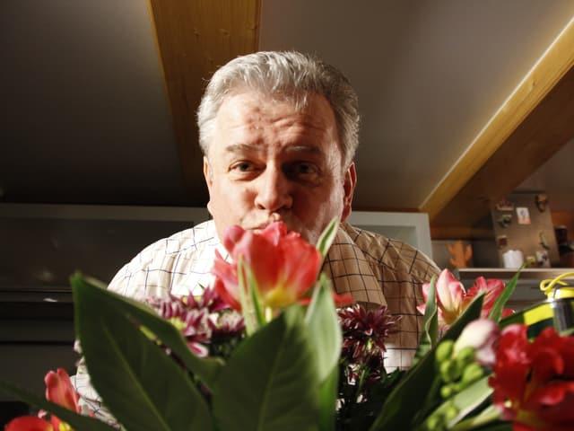 Harry Zartl schaut hinter einem Blumenstrauss hervor.