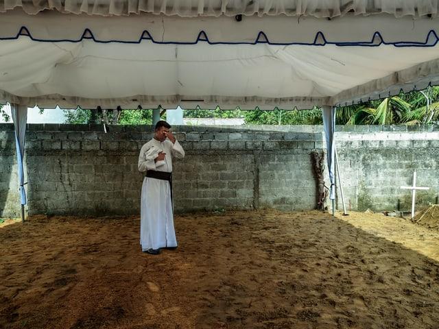 Ein erschöpfter Priester bei einer Pause zwischen Beerdigungen