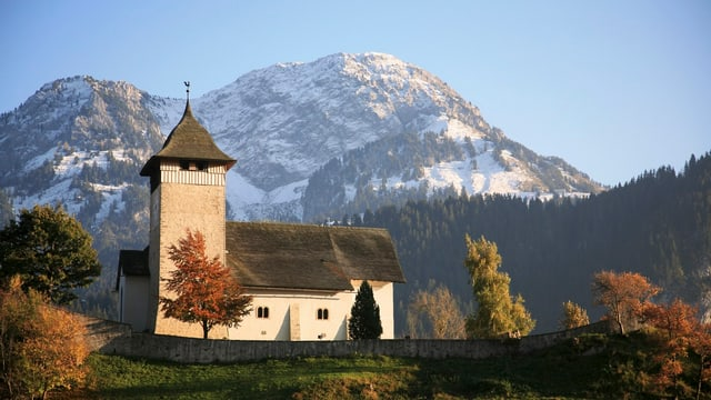 Die Kirche Temple de Château-d'Oex auf einer grünen Anhöhe vor verschneiten Bergen.