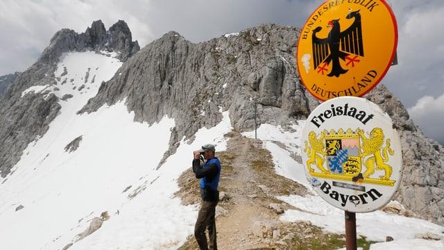 Grenzschutz-Polizist blickt mit Fernrohr vom Gipfel an der Deutsch-Österreichischen Grenze.