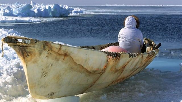 Inuit in einem Kanu, er schaut aufs Meer.