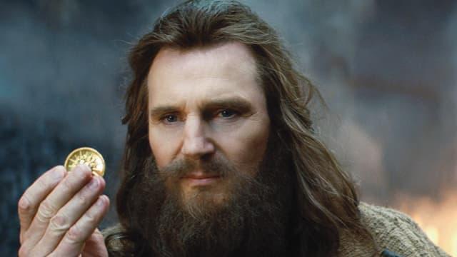 Mann schaut auf eine Münze, die er in der Hand hält