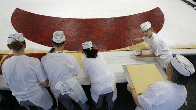 Junge Bäcker kreieren einen riesigen Spitzbueb.