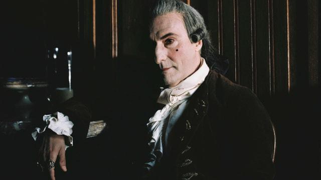 Casanova, stark geschminkt, sirtzt mit altertümlicher Kleidung in einem dunklen Raum.