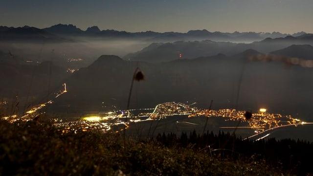 Blick von Berg hinab auf erleuchtete Siedlungen in der Nacht.