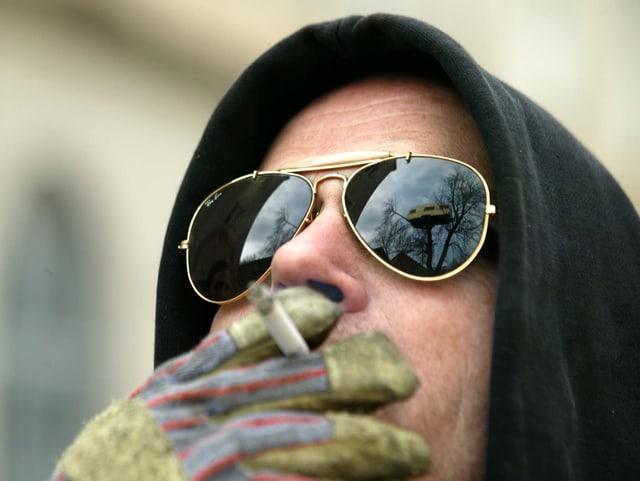 Flatz mit Kapuze und Sonnenbrille. Er trägt einen Arbeitshandschuh und zieht an einer Zigarette. In der Brille spiegelt sich die Installation «Belle Etage», ein Wohnwagen auf einem Baum.