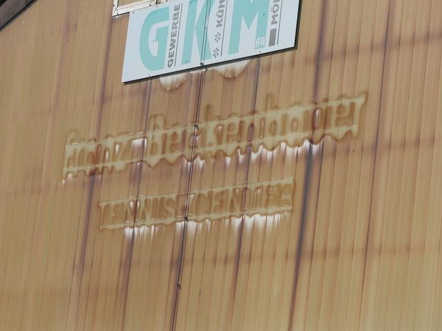 Abgefallener Schriftzug auf einer Tennishalle.