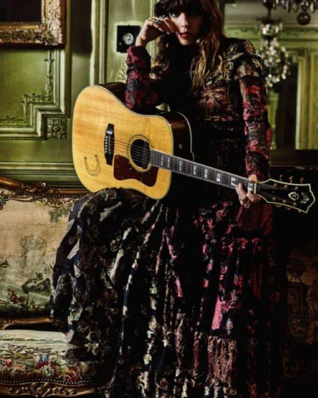 Lou mit Gitarre und wallendem Kleid