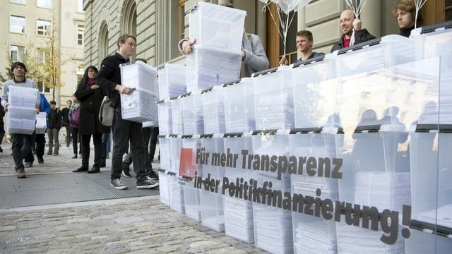 Personen laufen mit den Boxen, die Unterschriften enthalten, in Richtung Bundeshaus-West wahrend der Einreichung der Transparenz-Initiative.