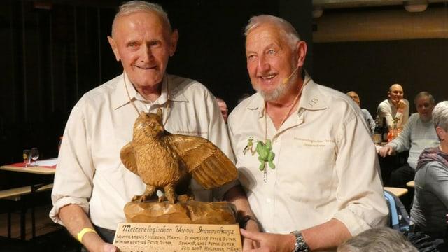 Zwei Männer mit einem Adler aus Holz.